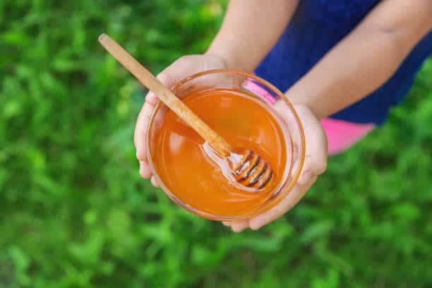 Copil cu un castron de miere