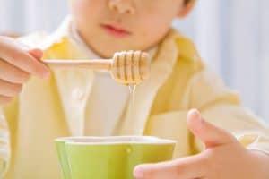 Copil care mananca miere